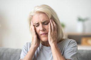 Old woman suffering headache due to elmiron.